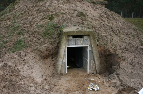Blick in einen Bunker bei geöffneter Tür. Oben ist der Fledermauseinflugschlitz erkennbar. Unten rechts befindet sich ein Einschlupfloch für Amphibien, welche frostsicher im Inneren überwintern.